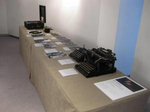 Photograph of exhibition of talking book records and player from RNIB, and also photographs and typewriters from Blind Veterans UK.